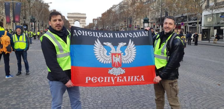 """Fabrice Sorlin (left) and Xavier Moreau (right) holding a flag of the so-called """"Donetsk People's Republic"""""""